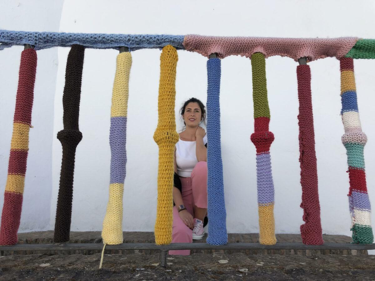 Irene sentada detras de una barandilla forrada de punto de colores