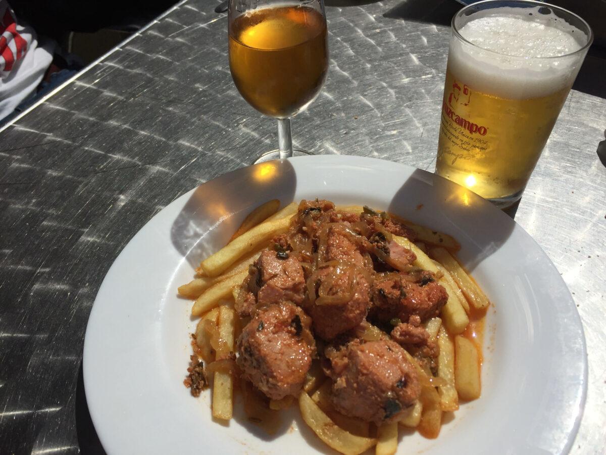 plato de atun encebollado con patatas fritas y cerveza y vino