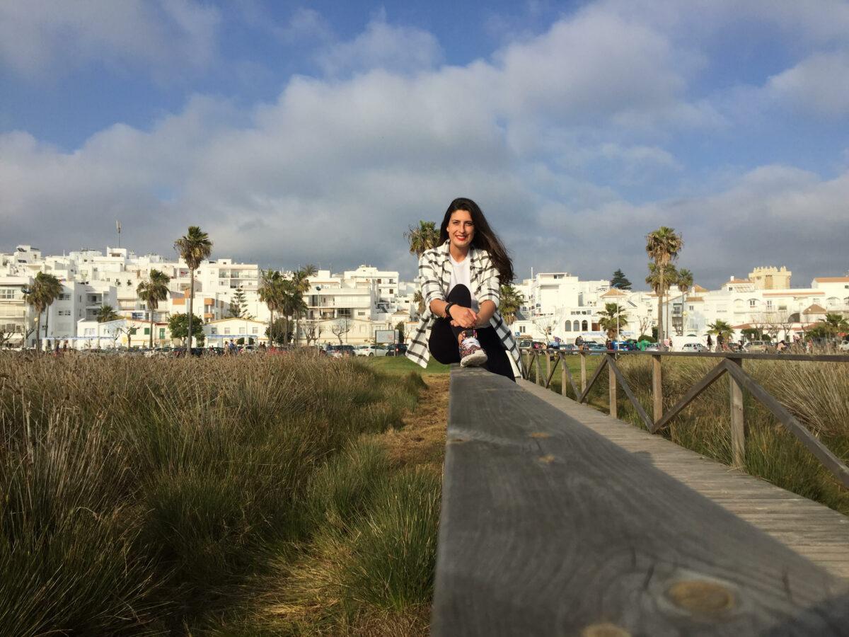 Irene sentada en barandilla camino de la playa con le pueblo de fondo