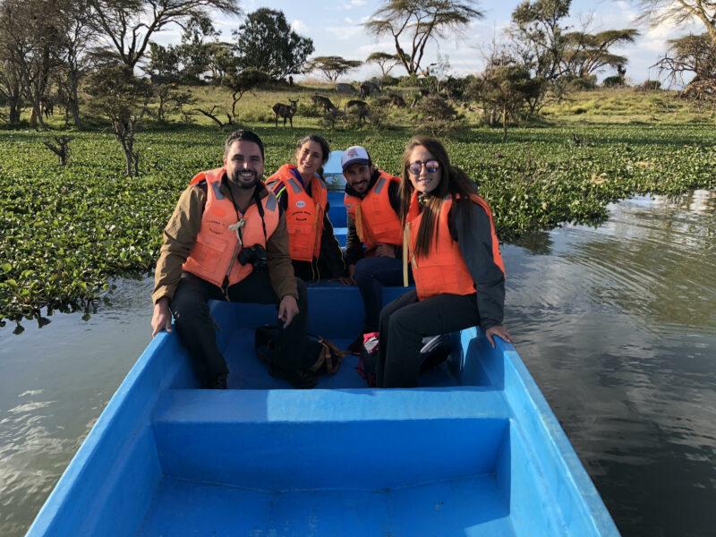 cuatro personas en una barca en el lago Naivasha con animales de fondo