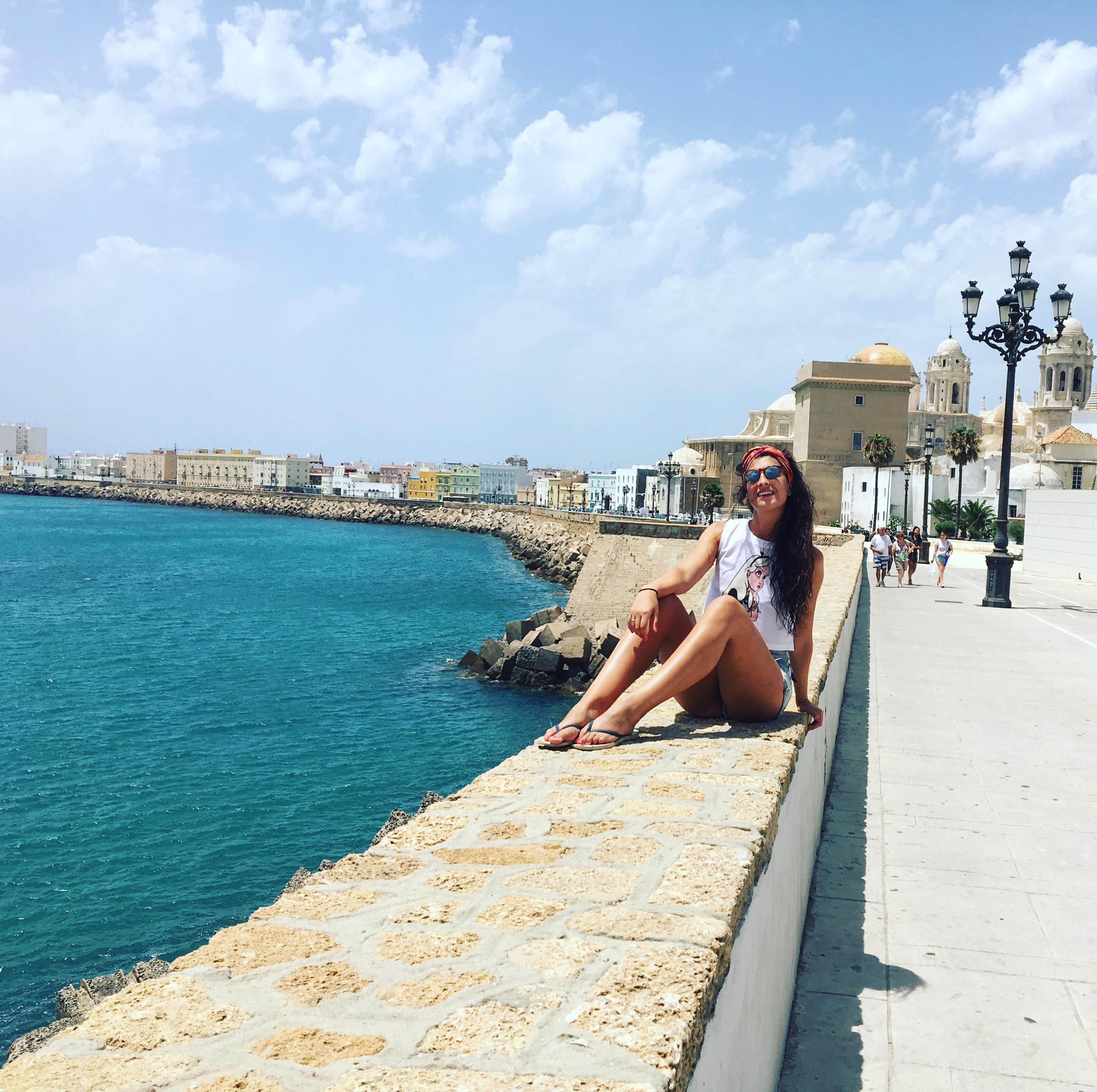 Irene sentada en un muro con el mar a un lado y la catedral de cadiz a otro