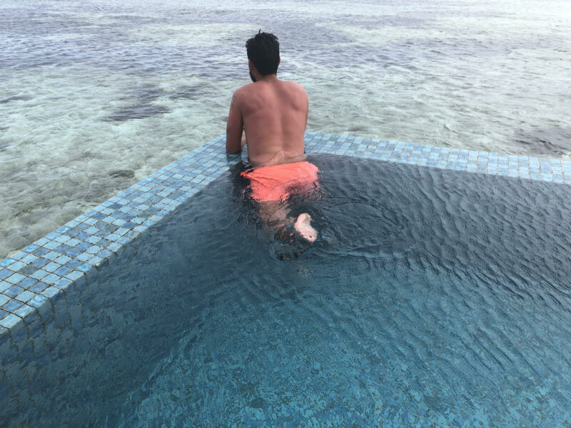Manolo de espaldas dentro de la piscina privada sobre el mar
